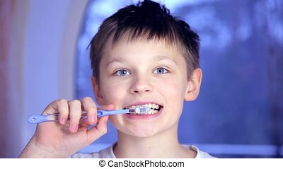 A boy on a blue background brushing his teeth