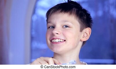 A boy on a blue background brushing his teeth, his teeth chattering and smiling broadly