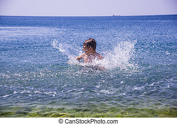 A boy on the beach, playing with the waves, summer time