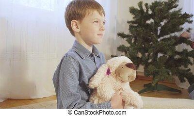 A boy on the floor near the Christmas tree