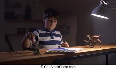 A Boy paints while sitting at a table under a desk lamp. Young artist