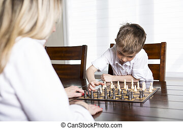 boy playing chess at home with mother