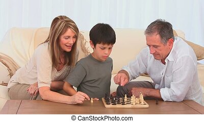 A boy playing chess with his grandfather