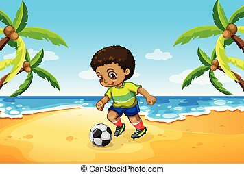 A boy playing football at the beach