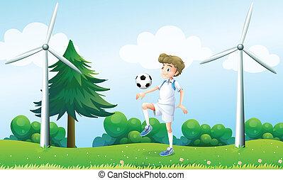 A boy playing football near the windmills