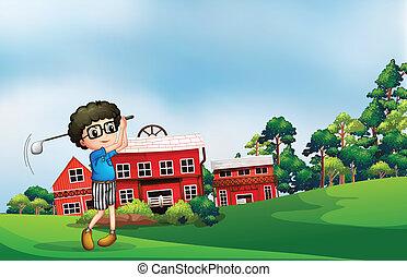 A boy playing golf near the barn