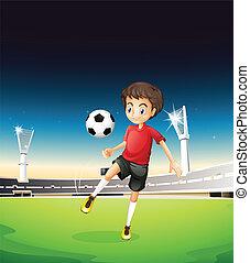 A boy playing soccer alone