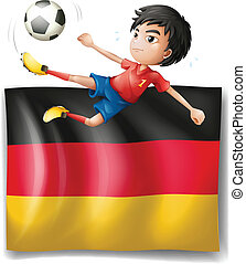 A boy playing soccer in front of the flag of Germany