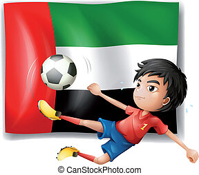 A boy playing soccer in front of the UAE flag