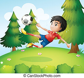 A boy playing soccer near the pine trees