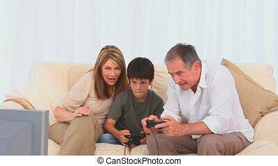 A boy playing video game with his grandfather