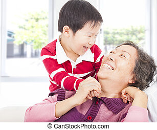 a boy playing with grandmother at home