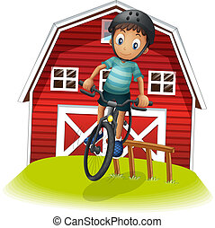 A boy playing with his bike in front of the barnhouse