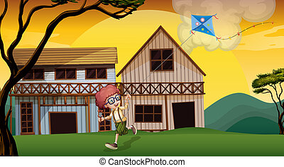 A boy playing with his kite in front of the wooden barnhouses