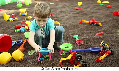 A boy plays on children's educational playground with toys...