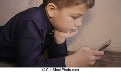 A boy plays on the smartphone