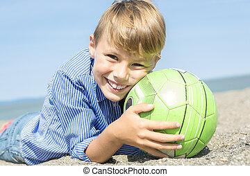 boy plays soccer on the beach