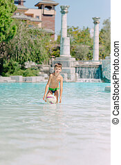 A boy plays with a ball in the water