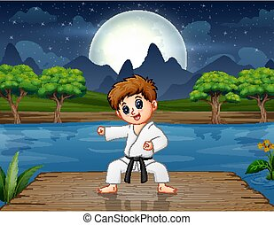 A boy practicing karate on the pier at night