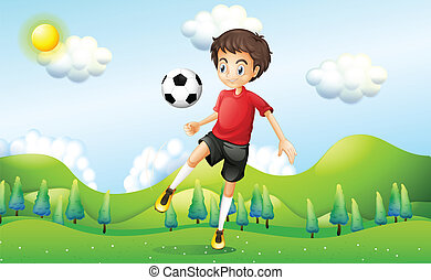 A boy practicing soccer at the hill