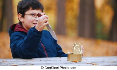 A boy pulls a knife out of the table and eats canned stewed...