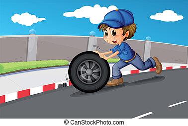 A boy pushing a wheel along the road