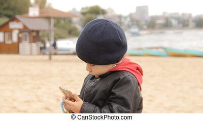 A boy pushing buttons in the smartphone, turning, telling something and holding multicolored toy rings in his hands.