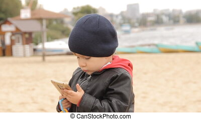 A boy pushing buttons in the smartphone on a sandy beach by...