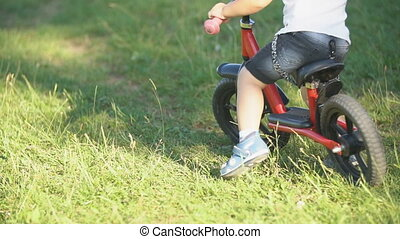a boy rides a bicycle without pedals