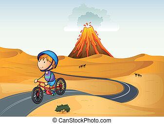 A boy riding a bike in the desert