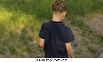 A boy running in a summer park
