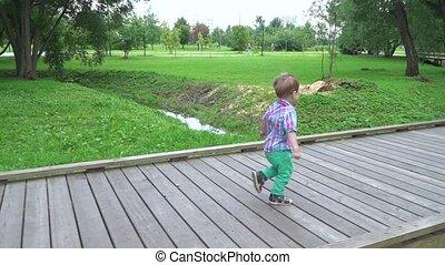 A boy runs on a wooden platform