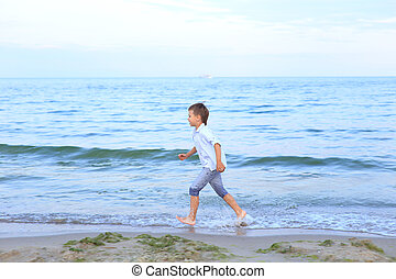 A boy runs on the water near the sea. A barefoot child walks...
