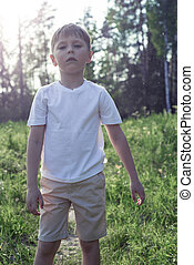 A boy seven years walking in the forest