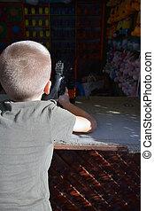 a boy shooting baloons