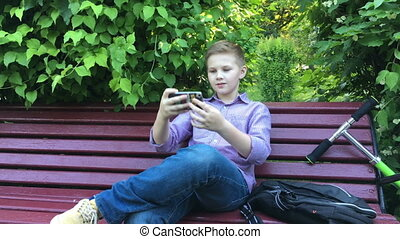 A boy sits on the bench and makes selfie