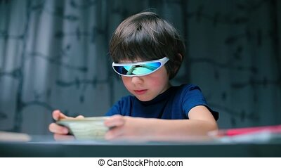 A boy sitting at a table with glasses uses a smartphone