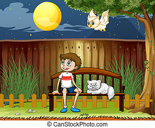 A boy sitting with his cat inside the fence