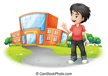 A boy standing in front of the school