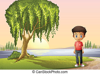 A boy standing near the giant tree