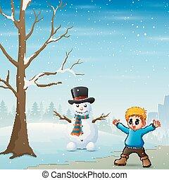 A boy standing near the snowman in winter landscape