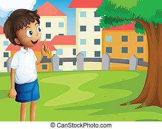 A boy standing near the tree