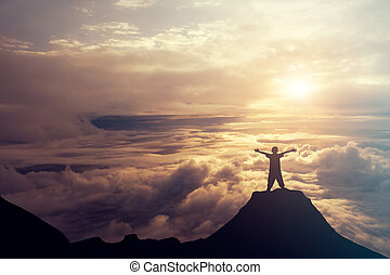A boy standing on the top of the mountain above the clouds. Success Concept.