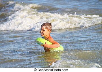A boy swims in the sea