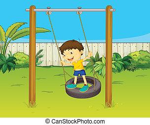 A boy swings on a wheel