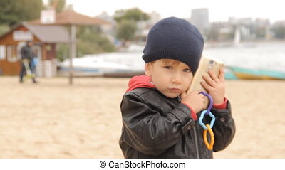 A boy talking on the smartphone, putting an incoming call on...