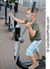 A boy train on outdoor equipment
