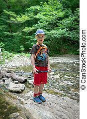 A boy traveler passes the stream ford