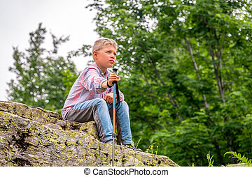 A boy traveler with a backpack and trekking poles is resting on a stone