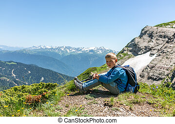 A boy traveler with hiking poles and a backpack is resting in the summer on top of a mountain with snow.